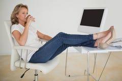 Zufällige Geschäftsfrau, die einen Kaffee mit ihren Füßen oben am Schreibtisch trinkt Lizenzfreie Stockfotografie