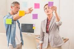 Zufällige Geschäftskollegen, die mit klebrigen Anmerkungen arbeiten Stockbilder