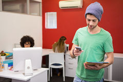 Zufällige Geschäftsmannversenden von sms-nachrichten im Büro Lizenzfreie Stockbilder
