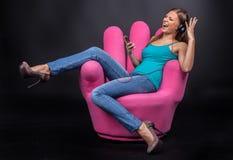 Zufällige junge Frau, die auf MP3-Player hört Lizenzfreies Stockbild