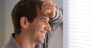 Zufälliger Geschäftsmann, der Fenster lächelt und heraus anstarrt Stockfotografie
