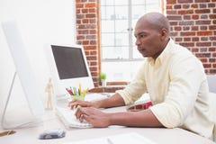 Zufälliger Geschäftsmann, der an seinem Schreibtisch arbeitet Stockbilder