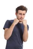 Zufälliger junger Mann bereit, die Verteidigung mit der Faust oben zu kämpfen Stockfoto