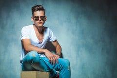 Zufälliger junger Mann, der auf einem hölzernen Kasten sitzt Lizenzfreie Stockfotos