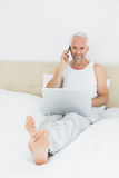 Zufälliger lächelnder reifer Mann, der Mobiltelefon und Laptop im Bett verwendet Stockfotos