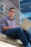 Zufälliger Student, der draußen an Laptop arbeitet Lizenzfreies Stockfoto