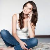 Zufälliges Brunettemädchen, das Handy hält Lizenzfreie Stockfotos