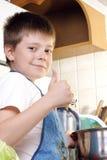 Zufrieden gestellter Junge an der Küche Stockbild