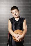 Zufrieden gestelltes Kind, das Basketball hält lizenzfreie stockbilder