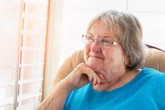 Zufriedene ältere Frau, die aus ihrem Fenster heraus anstarrt Stockfotos