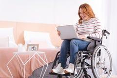 Zufriedene behinderte Frau, die ihren Laptop verwendet Stockbilder