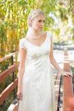 Zufriedene blonde Braut in der Perlenhalskette, die auf einer Brücke steht Lizenzfreie Stockbilder