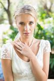 Zufriedene blonde Braut mit der Hand auf dem Kasten, der Kamera betrachtet Stockbilder