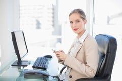Zufriedene blonde Geschäftsfrauversenden von sms-nachrichten Stockfotos
