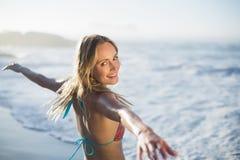 Zufriedene blonde Stellung auf dem Strand im Bikini mit den Armen heraus Stockfoto