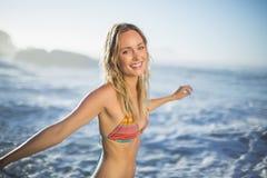 Zufriedene blonde Stellung auf dem Strand im Bikini mit den Armen heraus Stockbild