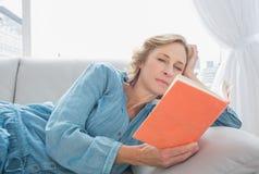 Zufriedene Blondine, die auf ihrem Couchlesebuch sich entspannen Stockbilder