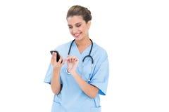 Zufriedene braune behaarte Krankenschwester im Blau scheuert sich unter Verwendung eines Handys Lizenzfreie Stockbilder