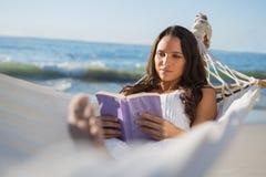 Zufriedene Frau, die auf Hängemattenlesebuch liegt Stockfotografie
