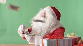 Zufriedene werfende Rechnungen Santa Clauss aus einem Bündelgeld auf Tabelle, Geld auf Tabelle, chromakey im Hintergrund heraus stock video