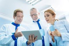 Zufriedene Wissenschaftler in den Uniformen, die Tablette und Schalen halten Stockbild