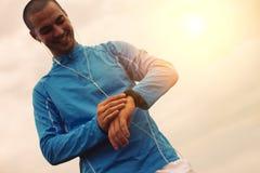 Zufriedener Athlet betrachtet intelligente Uhr Stockfotos