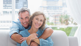 Zufriedener Mann, der seine Frau auf der Couch umarmt Stockbild