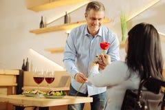 Zufriedener Mann, der seiner Frau eine Rose gibt Stockfotografie