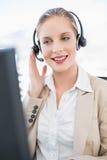 Zufriedenes blondes Call-Center-Mittel, das auf Kunden einwirkt Stockbilder