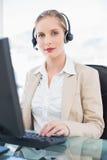 Zufriedenes blondes Call-Center-Mittel, das an Computer arbeitet Stockfotografie