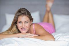 Zufriedenes blondes Lügen auf ihrem Bettlächeln Lizenzfreie Stockfotografie