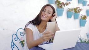Zufriedenes M?dchen, das mit Laptop drau?en sich entspannt stock footage
