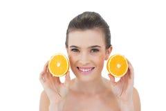 Zufriedenes natürliches braunes behaartes Modell, das orange Hälften hält Stockfotografie