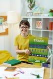 Zufriedengestellter dunkelhaariger kleiner Student, der ausdrucksvoll Plakat darstellt stockfotografie