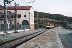 Zug, der alte Bahnhofsplattform in Landschaft einträgt Stockfotografie