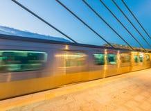 Zug, der auf einer Station nachts beschleunigt Unscharfer Bewegungseffekt Lizenzfreie Stockfotografie