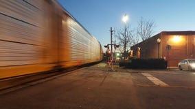 Zug, der an Bahnübergang an Dämmerung 1 sich vorbeibewegt Stockfotografie