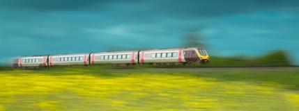 Zug, der durch gelbe Felder beschleunigt Stockfotos