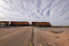 Zug, der eine Straße im New Mexiko kreuzt lizenzfreies stockfoto