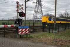 Zug, der einen Bahnübergang führt Lizenzfreie Stockbilder