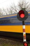 Zug, der hinter Bahnübergang hetzt Lizenzfreie Stockbilder