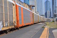 Zug, der mit Stadtzentrum im Hintergrund überschreitet Stockbild