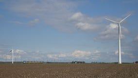 Zug der niederländischen Eisenbahnen mit Windkraftanlagen stock video footage