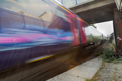 Zug, der in Unschärfe unter Brücke beschleunigt Lizenzfreies Stockbild