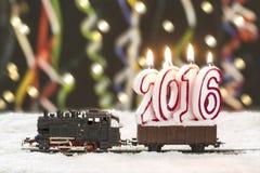 Zug 2016 mit schneebedeckten Schienen auf buntem Hintergrund Lizenzfreie Stockfotografie