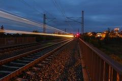 Zug schleppt in der Nacht auf langer Belichtung mit rotem Licht Stockfotos
