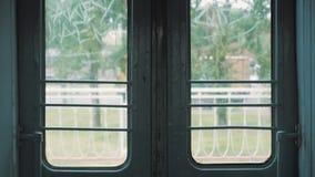 Zug schließt automatische Türen und fängt an, entlang weißen Zaun, grüne Bäume 4k sich zu bewegen stock footage