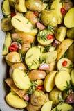 Zugebereitete backende Kartoffeln mit Rosmarin und Knoblauch Stockbilder