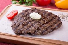 Zugebereitetes Steak diente mit Butter an Bord stockbild