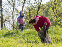 Zugres, Ukraine - April 26 2014: Mother and daughter scavenge in the city park Royalty Free Stock Photography
